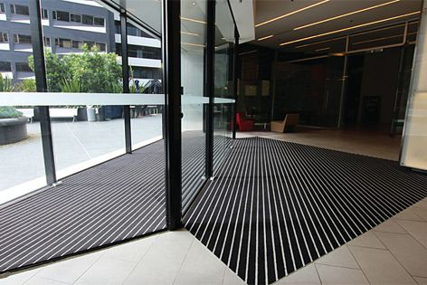An installation of Integra Vantt architectural entrance matting at a modern office tower.