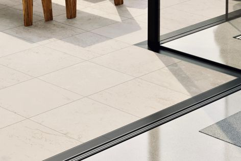 Threshold drains from Stormtech create non-trip transitions between indoor and outdoor living areas.
